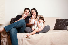 Happy family snacking on sofa couch Stock Photos