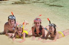 Happy family in snorkels on tropical beach Royalty Free Stock Images