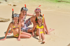 Happy family in snorkels on tropical beach on vacation Royalty Free Stock Images