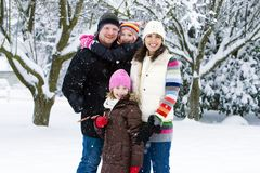 Happy family in the snow. A happy family of four smiling in a snow storm Royalty Free Stock Photos