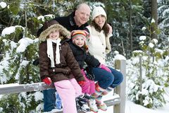 Happy family in the snow. A happy family of four smiling while sitting on a snow covered fence Royalty Free Stock Images