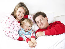 Happy Family snuggle. A smiling family snuggling under the a blanket in bed Stock Photo