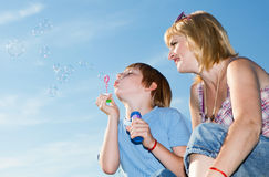 Happy family with soap bubbles against a sky. Boy and mother with soap bubbles against a sky Royalty Free Stock Photos