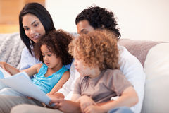 Happy family on the sofa looking at photo album Royalty Free Stock Image