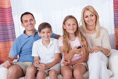 Happy Family On A Sofa Watching Tv Stock Photos