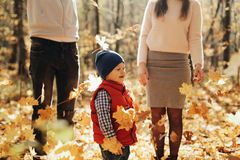 Happy family with son in autumn park throws yellow leaves. stock image