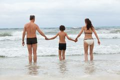 Happy family with son having fun in water Stock Images