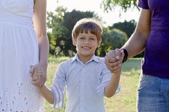 Happy family with son and parents holding hands. Family fun, happy mother, father and son holding hands in park and looking at camera. Waist up, front view Stock Photos