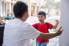 Son running and hugging dad. Happy family son running and hugging dad after going back from school stock photos