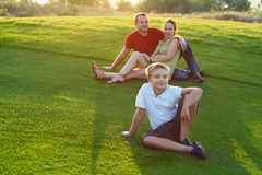 Happy family with son sitting on grass in the park Stock Photography
