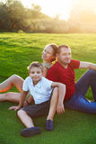 Happy family with son sitting on grass in the park Stock Photos