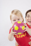 Happy family spanish soccer fan. Happy blonde baby sixteen month old and mother with red shirt of Spanish soccer team with ball Royalty Free Stock Photo
