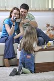 Happy family special moments on video. Young happy family recording by video camera their child at home Stock Image