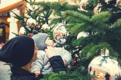 Happy family spend time at a Christmas and New Year holidays. The first Christmas and New Year! Cute baby looking at a reflection in a bowl on a Christmas tree stock photo