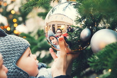Happy family spend time at a Christmas and New Year holidays. The first Christmas and New Year! Cute baby looking at a reflection in a bowl on a Christmas tree royalty free stock photo