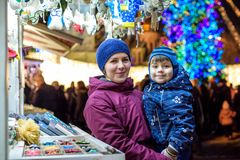 Happy family spend time at a Christmas street market fair in the. Old town. Holidays, Christmas, Family concept. Mother and son at winter outdoor among Stock Image