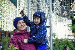 Happy family spend time at a Christmas street market fair in the. Old town. Holidays, Christmas, Family concept. Mother and son at winter outdoor among Royalty Free Stock Image
