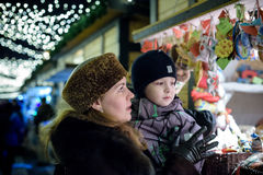 Happy family spend time at a Christmas street market fair in the Stock Photos
