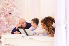 Happy family spend time together behind laptop, lying on bed in stock images