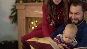 Happy family spend time together reading book. Father sitting in armchair, holding little baby son on his laps, mother. Happy family spends time together reading stock video