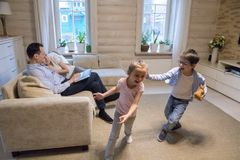 Happy family spending time at home having fun together. Happy family of four relaxing spending time at home together, parents lying on cozy couch resting stock photography