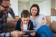 Family spending time at home and looking something fanny on tablet. Happy family spending time at home and looking something fanny on tablet royalty free stock image