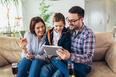 Family spending time at home and looking something fanny on tablet. Happy family spending time at home and looking something fanny on tablet royalty free stock photo