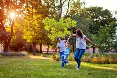 Happy family spending time outdoors playing in park. Mom having fun with two kids. Family values. Happy family spending time outdoors playing in park. Mom having royalty free stock photo