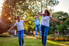 Happy family spending time outdoors playing in park. Mom having fun with two kids. Throwing toddler up. Family values royalty free stock photos