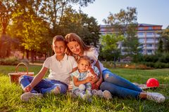 Happy family spending time outdoors sittting on grass in park. Mom with two children smiling. Mother`s day. Happy family spending time outdoors sittting on grass stock photo
