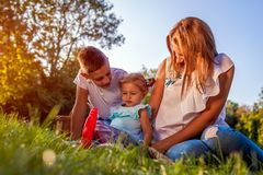 Happy family spending time outdoors sittting on grass in park. Mom with two children smiling. Mother`s day. Happy family spending time outdoors sittting on grass royalty free stock photo