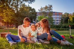 Happy family spending time outdoors sittting on grass in park. Mom with two children smiling. Family values. Happy family spending time outdoors sittting on stock photo