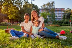 Happy family spending time outdoors sittting on grass in park. Mom with two children smiling. Family values. Happy family spending time outdoors sittting on royalty free stock image