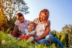 Happy family spending time outdoors sittting on grass in park. Mom with two children smiling. Family values. Happy family spending time outdoors sittting on royalty free stock images