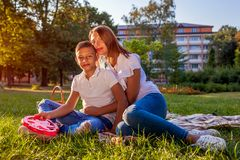 Happy family spending time outdoors sittting on grass in park. Mother with her son hugging and smiling. Family values. Happy family spending time outdoors stock images