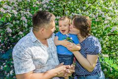Happy mom and dad hugging baby in Park on summer Sunny day. Happy family spending time outdoors on a Sunny summer day. Couple giving two young children piggyback Royalty Free Stock Photography