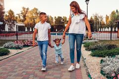 Happy family spending time outdoors walking in park. Mother and her son holding little toddler girl. Family values. Chilling together royalty free stock photos