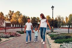 Happy family spending time outdoors walking in park. Mother and her son holding little toddler girl. Family values. Chilling together stock photo