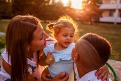 Happy family spending time outdoors walking in park. Mother and her son hugging little toddler girl and talking. Happy family spending time outdoors walking in royalty free stock images