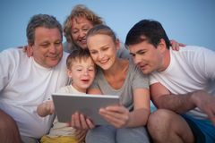 Happy family spending time with pad outdoor. Happy big family having good time together. Grandparents and parents looking at the pad screen while boy using it Stock Photo