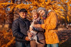 Happy family spending time with pug dog in autumn park. Parents with their son hugging pet. Family values stock photography