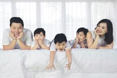 Happy family spending time together on the bed. Image of happy family spending time together while lying on the bed Royalty Free Stock Images