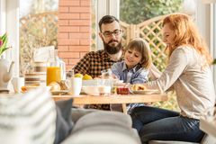 Happy family spending time together. Happy, young family spending time together, eating a meal in an arbor stock photos