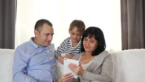 Happy family spending time together. Mother, father and child use the tablet to watch a movie, play a game or use the