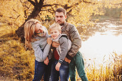 Happy family spending time together outdoor. Lifestyle capture, rural cozy scene. Father, mother and son walking in forest stock photo
