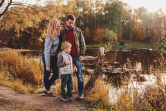 Happy family spending time together outdoor. Lifestyle capture, rural cozy scene. Father, mother and son walking in forest stock photography