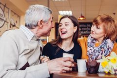 Happy family spending time together. Senoir family couple with adult daughter chat and laugh in cafe. Family values stock photos