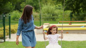 Happy Family Spending Time Together During Summer Warm Day on the Playground. Little Girl Riding a Swing Outdoors. stock footage