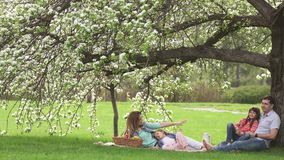 Happy family spends time on a picnic near the blossoming apple-tree. Dad, mom and two daughters spend their time outdoor. Happy family spends on a picnic near stock video