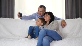 Happy family spends time together sitting on the couch. A father photographs his wife and son taking selfies. Technology